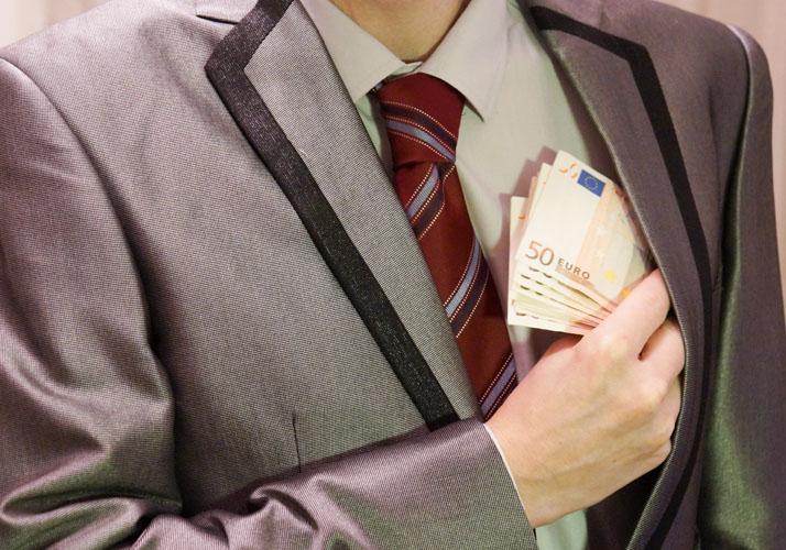 Mann steckt Geldbündel in Jackettasche