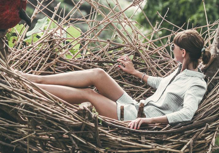 Frau liegt in Nest aus Zweigen