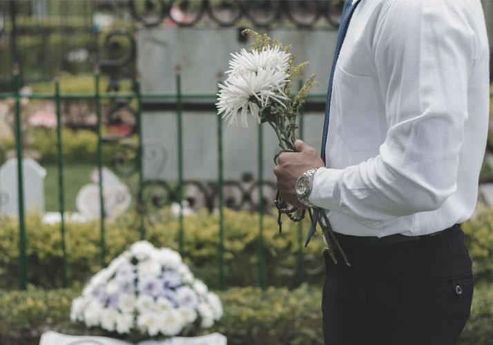 Mann mit Blumen auf Friedhof